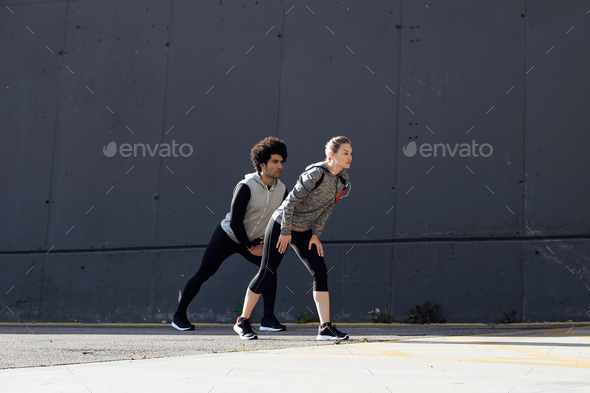 Fit and sporty couple stretching in the street. - Stock Photo - Images