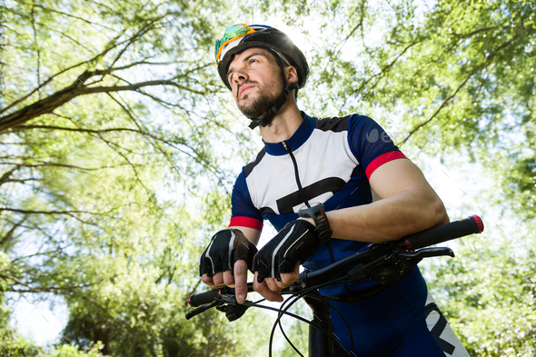 Handsome young man relaxing after cycling in the mountain. - Stock Photo - Images