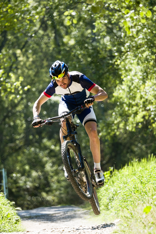 Handsome young man cycling in the mountain. - Stock Photo - Images