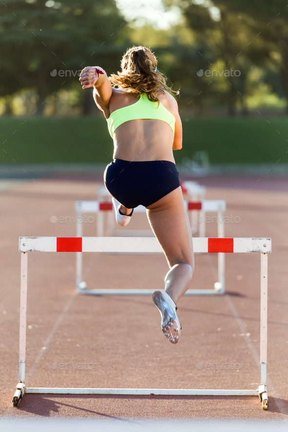 Young athlete jumping over a hurdle during training on race trac - Stock Photo - Images