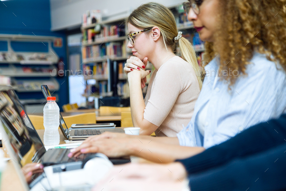 Two beautiful young women studying in a university library. - Stock Photo - Images