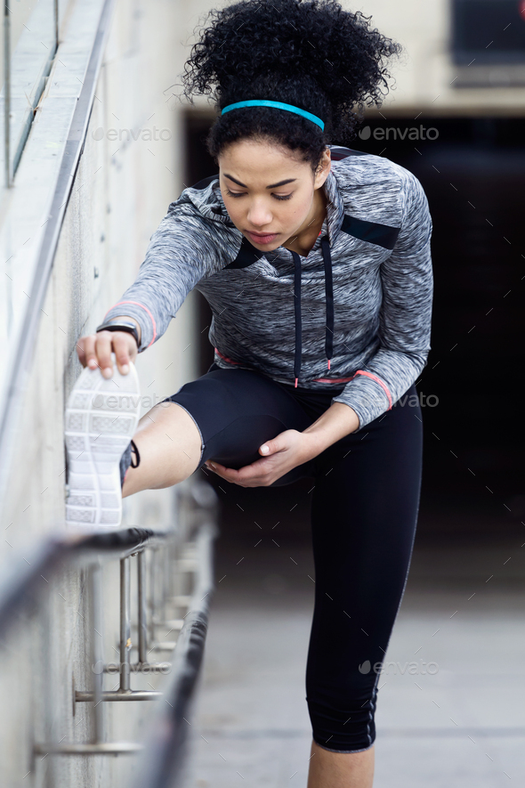 Fit and sporty young woman doing stretching in city. - Stock Photo - Images