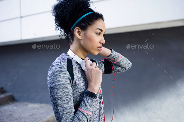 Fit and sporty young woman listening to music with mobile phone. - Stock Photo - Images