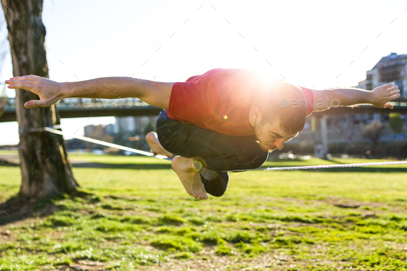 Handsome young man walking on slackline in the park. - Stock Photo - Images