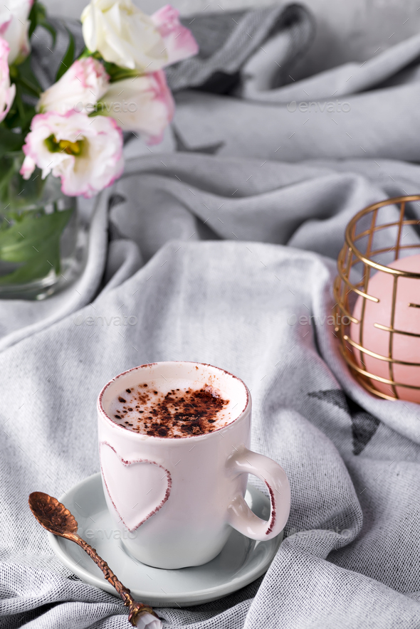 Having a cup of coffee with chocolate, flowers eustoma and candle on blanket in bed. Holiday concept - Stock Photo - Images