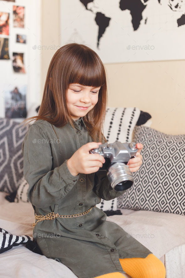 Child girl holding a retro camera sitting on bed at home - Stock Photo - Images