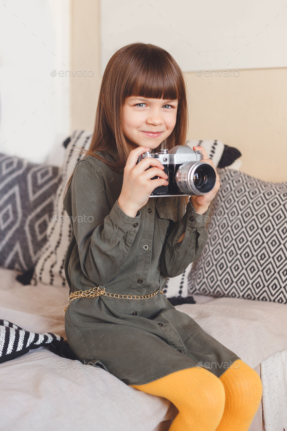 Little lady photographer with camera in room - Stock Photo - Images