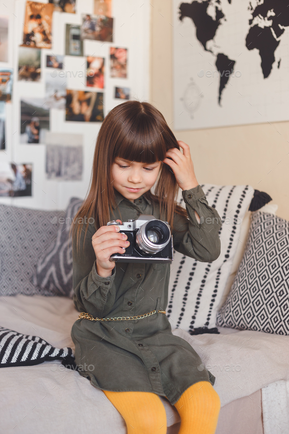 Little girl with an old camera. Wants to be a photographer - Stock Photo - Images