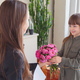 Daughter gifts flowers and card to her mother in living room. Child congratulates mom on a holiday - PhotoDune Item for Sale
