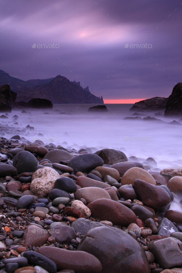 Sunset on the rocky shore of tropical sea - Stock Photo - Images