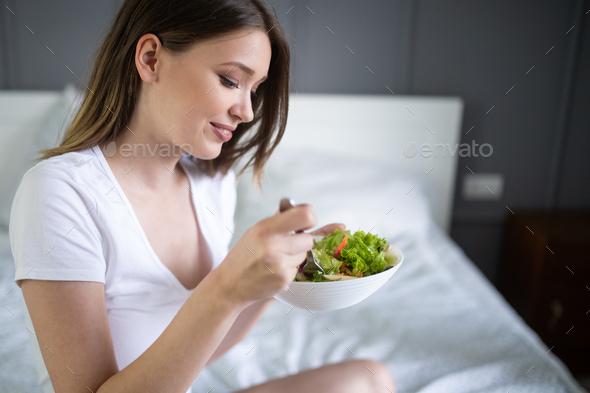 Beautiful woman eating healthy fresh organic salad - Stock Photo - Images
