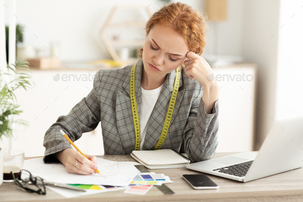Thoughtful seamstress drawing sketches in dressmaking studio - Stock Photo - Images
