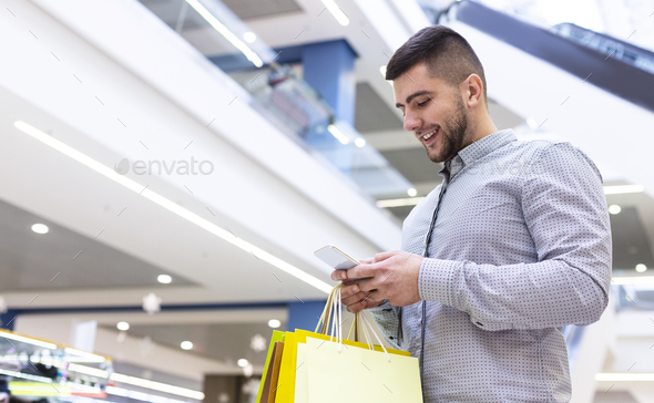 Handsome man using phone, shopping in mall - Stock Photo - Images