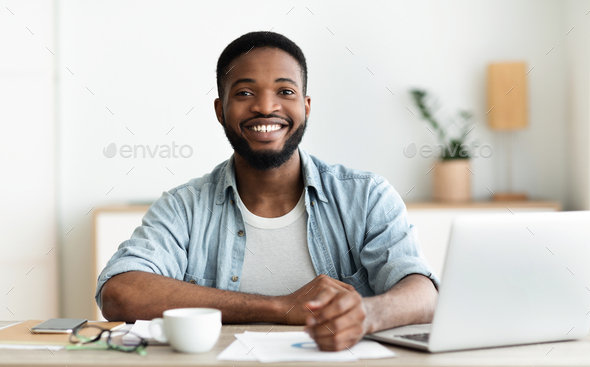 Positive black guy posing to camera at workplace - Stock Photo - Images