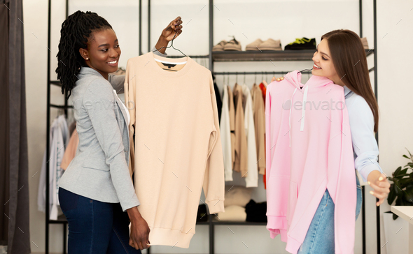 Personal Fashion Stylist Choosing Seasonal Updates For Client In Showroom - Stock Photo - Images
