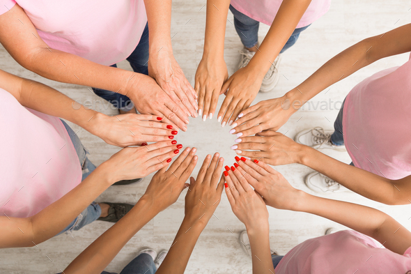 Women In Pink T-Shirts Holding Hands In Circle Indoor, Top-View - Stock Photo - Images