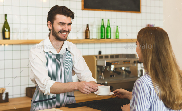 Waiter giving aromatic coffee to girl and widely smiling to her - Stock Photo - Images