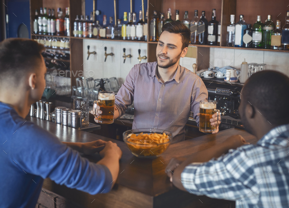 Bartender Giving Glasses With Beer To Young Guys - Stock Photo - Images