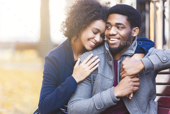 Curly black girl hugging her man with big love - Stock Photo - Images