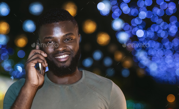 Cheerful afro guy talking on smartphone over night city background - Stock Photo - Images