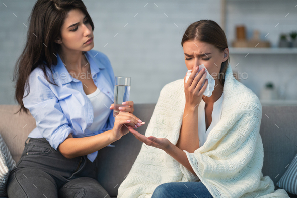 Girl Giving Pills To Sick Roommate Sitting On Couch Indoor - Stock Photo - Images