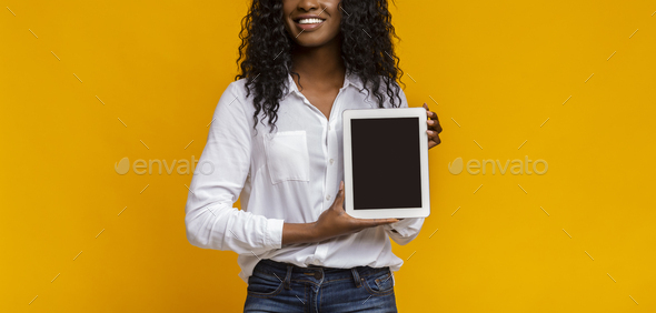 African woman showing blank digital tablet screen - Stock Photo - Images