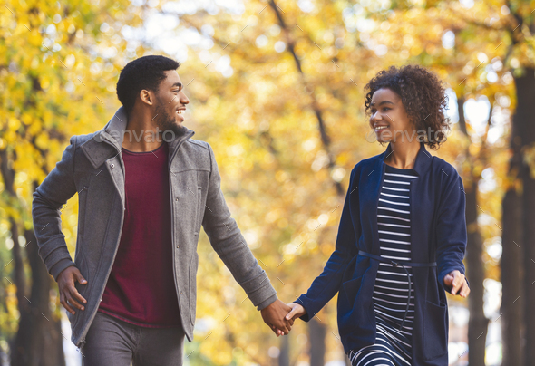 Black couple in holding hands while walking by autumn forest - Stock Photo - Images