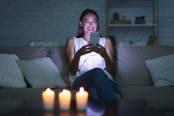 Happy Girl Texting On Cellphone In Dark Room - Stock Photo - Images