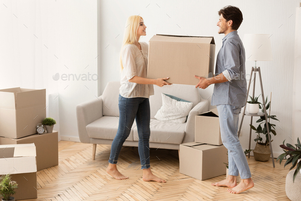 Husband And Wife Carrying Moving Box Together Into New Apartment - Stock Photo - Images