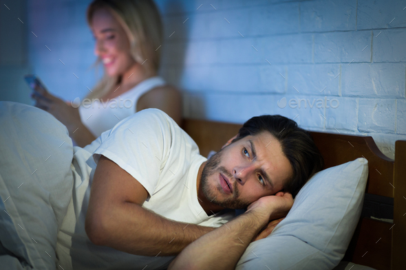 Girlfriend Texting On Phone Lying With Boyfriend In Bed, Low-Light - Stock Photo - Images