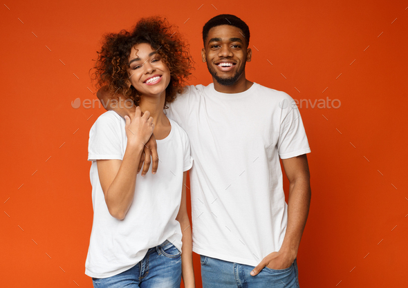 Happy african millennials embracing on orange background - Stock Photo - Images