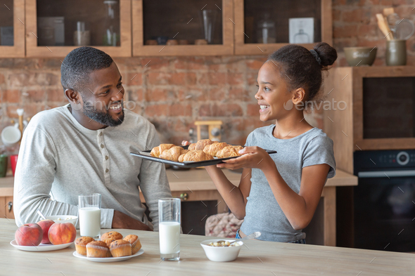 Happy girl showing dad freshly baked croissants - Stock Photo - Images