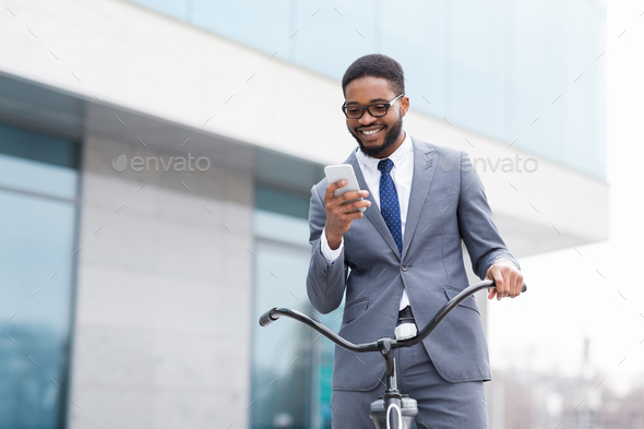 Excited businessman using phone against office building - Stock Photo - Images