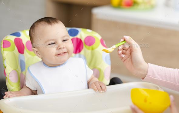 Mother feeding cute baby with tasty porridge - Stock Photo - Images