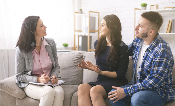Cheerful young spouses talking to professional marital counselor - Stock Photo - Images