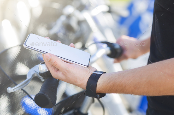 Cyclist texting on smartphone, riding on bicycle - Stock Photo - Images