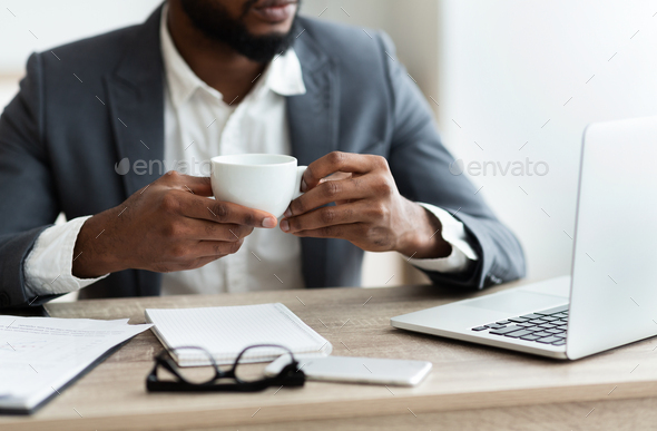 African american employee having coffee at workplace in office - Stock Photo - Images