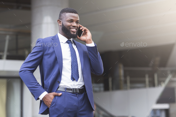 Young attractive businessman making phone call and smiling - Stock Photo - Images