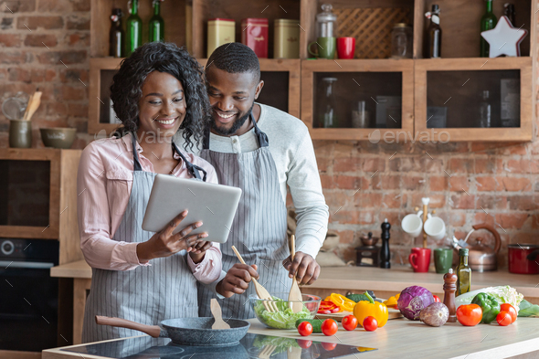 Black couple using digital tablet in kitchen - Stock Photo - Images