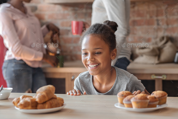 Charming girl looking with joy at sweets at kitchen - Stock Photo - Images