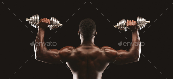 Back view of african fitness model pushing up the dumbbells - Stock Photo - Images