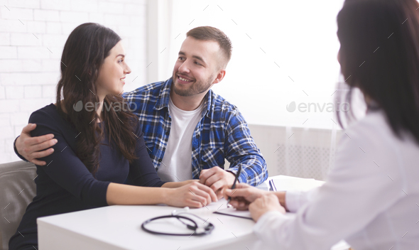 Young couple smiling at each other, happy to hear doctor's news - Stock Photo - Images