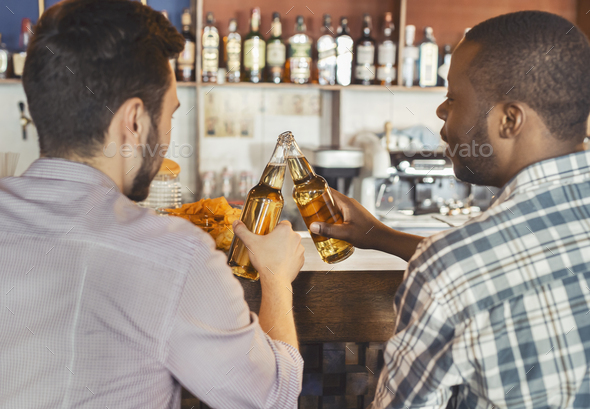 Back view of two guys drinking beer together in bar - Stock Photo - Images