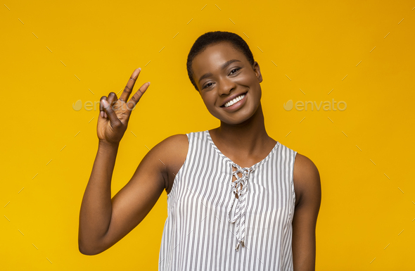 Smiling black girl posing at camera and demonstrating v-sign - Stock Photo - Images
