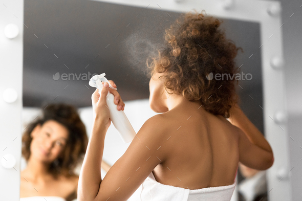Unrecognizable Afro Woman Using Hair Spray Standing In Bathroom - Stock Photo - Images