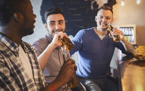 Friends talking while watching football game in bar - Stock Photo - Images