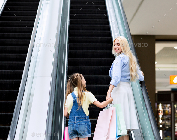 Cheerful Mother And Daughter Standing On Escalator In Shopping Mall - Stock Photo - Images
