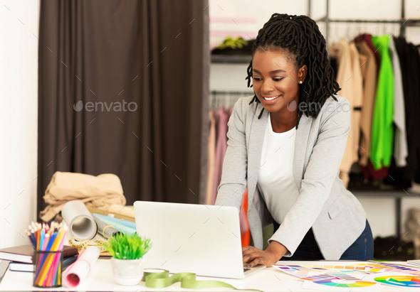 African American Dressmaker Using Laptop Working In Showroom - Stock Photo - Images