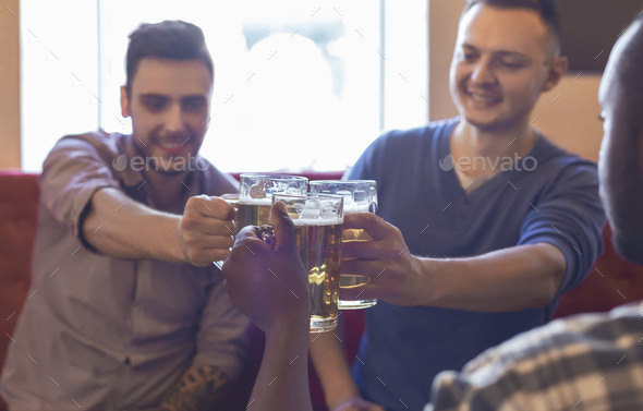 Happy mates clinking glasses with beer together - Stock Photo - Images