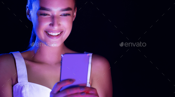 Woman texting on phone, face illuminated by screen light - Stock Photo - Images